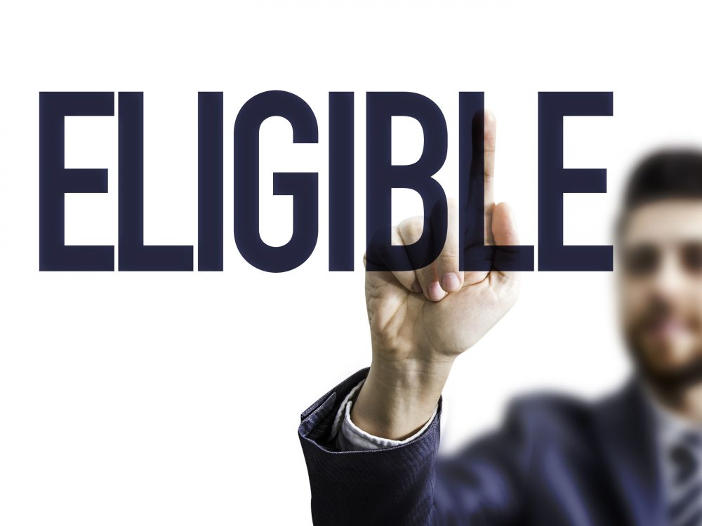 Business man pointing the text: Eligible